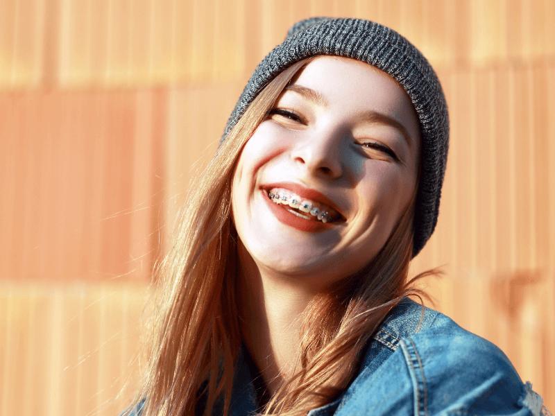 Imagem de jovem a sorrir com aparelho dentário