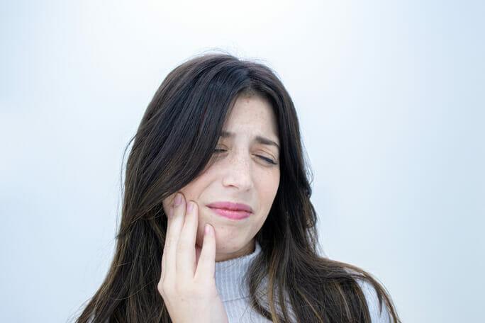 imagem de jovem mulher a queixar-se de dor nos dentes