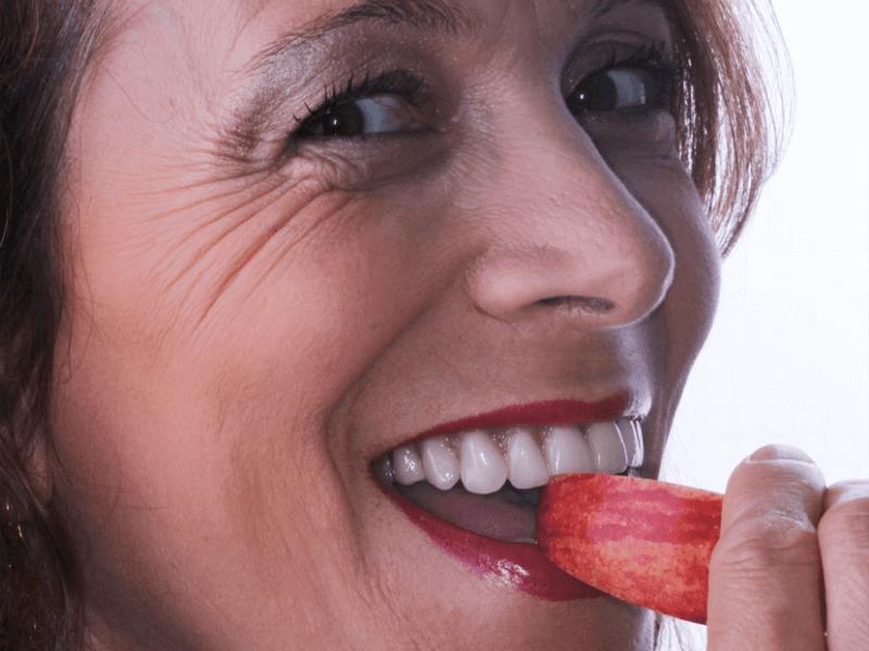 imagem de paciente a trincar uma maça depois de colocar implante dentário