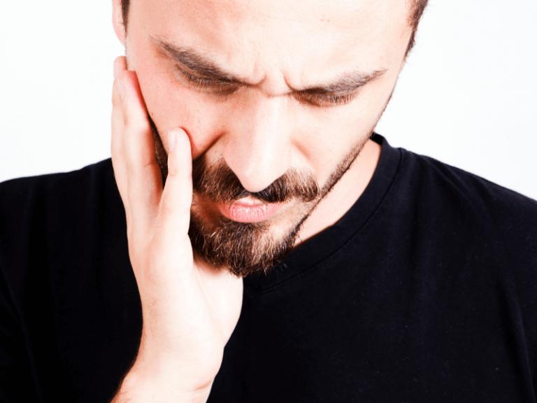 imagem de jovem com dor na boca causada pela periodontite